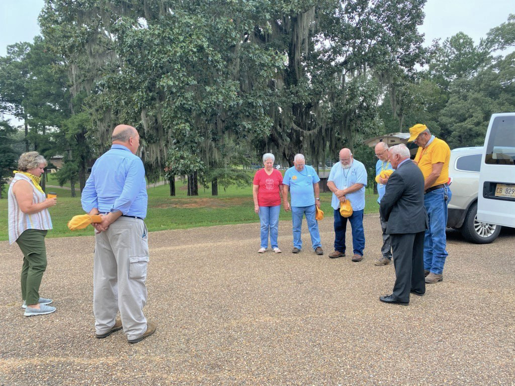 ON THEIR WAY – John Henry (right), chainsaw teams coordinator for Mississippi Baptist Disaster Relief (MBDR), prays Aug. 29 at Garaywa Camp and Conference Center in Clinton with the first contingent of MBDR volunteers to depart for Lake Charles, La., to help provide ministry at a 10,000-plus meals per day mass feeding operation in that community hit hard by Hurricane Laura on Aug. 27. (Photo by Roddy Reed)